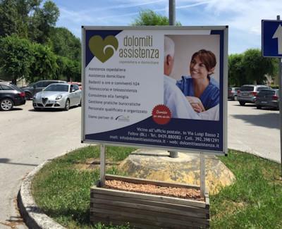Uno dei pannelli pubblicitari esposti all'ospedale di Feltre: questo si trova nel parcheggio